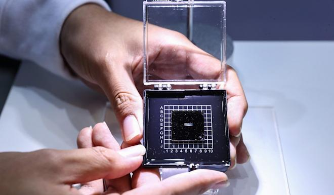A staff member shows a photonic AI chip during a press preview of the 2018 National Mass Innovation and Entrepreneurship Week in Beijing. Photo: Xinhua