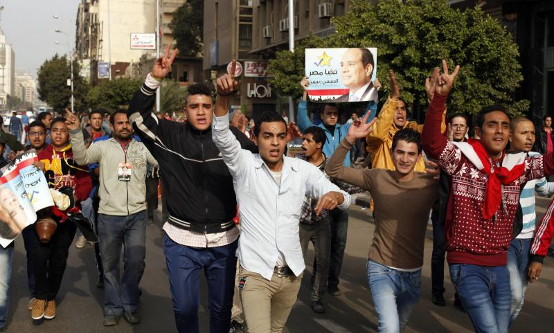 Pro-government protesters chant slogans while holding a picture for Egyptian President Abdel Fattah al-Sisi during a protest near Tahrir square in Cairo January 25, 2015. At least 15 people were killed in anti-government protests in Egypt on Sunday, the anniversary of the 2011 uprising that toppled autocrat Hosni Mubarak, security sources said. Riot police sealed off roads, including those leading to Cairo's Tahrir Square, the symbolic heart of the 2011 revolt. REUTERS/Asmaa Waguih (EGYPT - Tags: POLITICS CIVIL UNREST ANNIVERSARY)