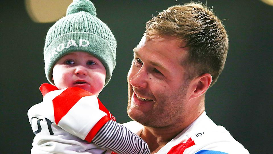 Seen here, Trent Merrin holds his child after a game for the Dragons.