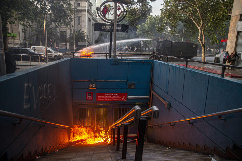 A police water cannon puts out a burning barricade near the Santa Lucia subway station during a protest against the rising cost of subway and bus fares, in Santiago, Friday, Oct. 18, 2019.  (Photo: Esteban Felix/AP)