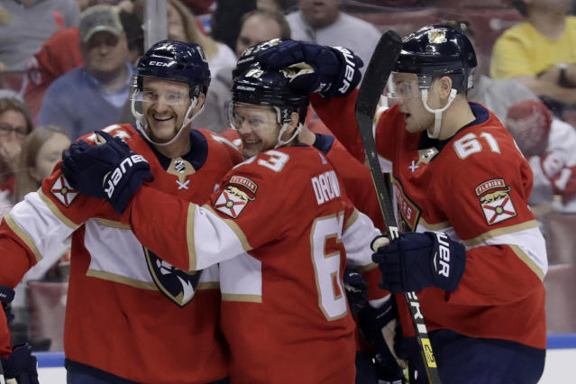 Florida Panthers center Jonathan Huberdeau, left, celebrates with right wing Evgenii Dadonov (63) and defenseman Riley Stillman (61) after scoring a goal during the second period of the team's NHL hockey game against the Detroit Red Wings, Saturday, Nov. 2, 2019, in Sunrise, Fla. (AP Photo/Lynne Sladky)