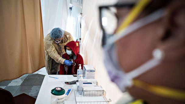 PHOTO: A doctor examines Juan Vasquez for a COVID-19 test inside a testing tent at St. Barnabas hospital, on March 20, 2020, in New York City. (Misha Friedman/Getty Images)