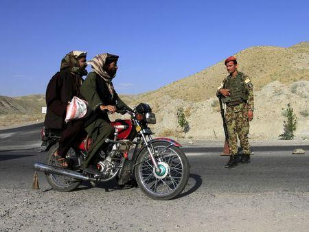 An Afghan National Army soldier (ANA) watches a motorcyclist at a checkpoint on the outskirts of Jalalabad province June 29, 2015. REUTERS/Pariwz