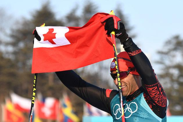 Tonga's Pita Taufatofua holds up his national flag after crossing the finish line during the men's 15km cross country freestyle at the Alpensia cross country ski centre during the Pyeongchang 2018 Winter Olympic Games on Feb.16, 2018 in Pyeongchang.