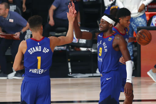 Denver Nuggets forward Michael Porter Jr. (1) and forward Jerami Grant (9) celebrate after defeating the San Antonio Spurs in an NBA basketball game Wednesday, Aug. 5, 2020, in Lake Buena Vista, Fla. (Kim Klement/Pool Photo via AP)