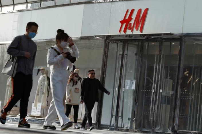 People walk past an H&M store in a shopping area in Beijing