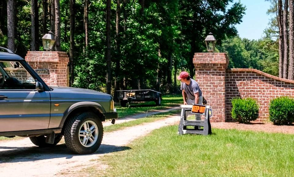 """A worker places a """"keep out"""" sign at the entrance to the main house to the Murdaugh property on Thursday, June 17, 2021 on Moselle Road in Islandton, S.C. On Monday, June 7, 2021, Maggie Murdaugh, 52, and her son Paul Murdaugh, 22, died from gunshot wounds in an apparent homicide in at their residence in Colleton County."""