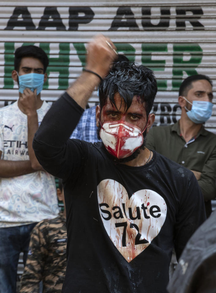 A Kashmiri Shiite Muslims wearing a mask flagellates himself during a Muharram procession in Srinagar, Indian controlled Kashmir, Saturday, Aug. 29, 2020. Muharram is a month of mourning in remembrance of the martyrdom of Imam Hussein, the grandson of Prophet Mohammed. Authorities had imposed restrictions in parts of Srinagar, the region's main city, to prevent gatherings marking Muharram from developing into anti-India protests. (AP Photo/Mukhtar Khan)