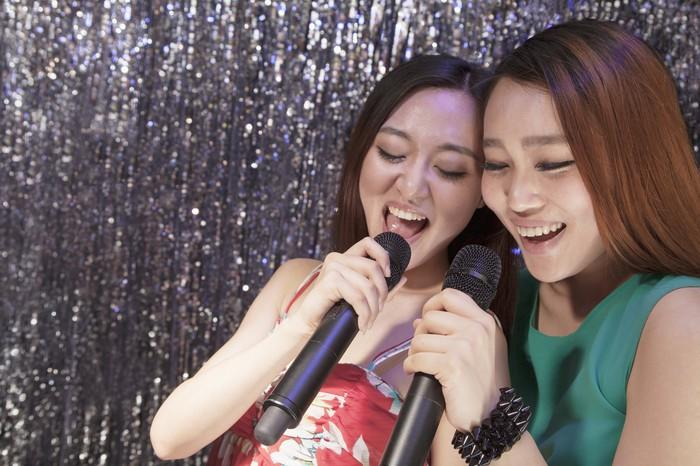 Two young women sing karaoke.
