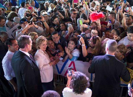 """Democratic U.S. presidential candidate Hillary Clinton greets the crowd with U.S. Secretary of Housing and Urban Development Julian Castro (FarL) during a """"Latinos for Hillary"""" rally in San Antonio, Texas October 15, 2015. REUTERS/Darren Abate"""