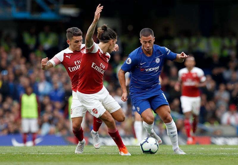 Chelsea's Eden Hazard, right, duels for the ball with Arsenal's Hector Bellerin during the English Premier League soccer match between Chelsea and Arsenal at Stamford bridge stadium in London, Saturday, Aug. 18, 2018. (AP Photo/Alastair Grant)
