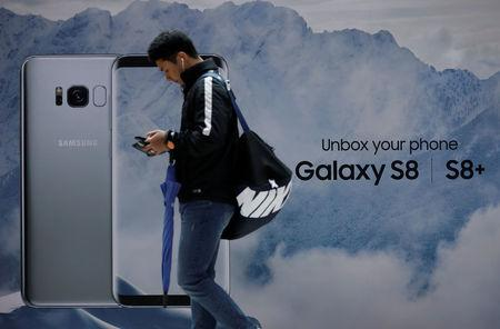 A man using his mobile phone walks past an advertisement promoting a Samsung Electronics' Galaxy S8 smartphone at a shop in Seoul