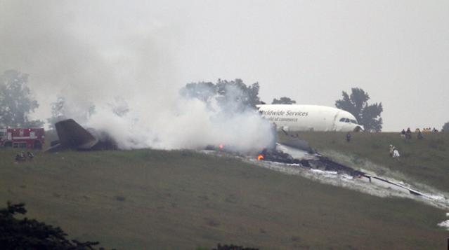 Debris burns as a UPS cargo plane lies on a hill at Birmingham-Shuttlesworth International Airport after crashing on approach, Wednesday, Aug. 14, 2013, in Birmingham, Ala. Toni Herrera-Bast, a spokeswoman for Birmingham's airport authority, says there are no homes in the immediate area of the crash. (AP Photo/Hal Yeager)