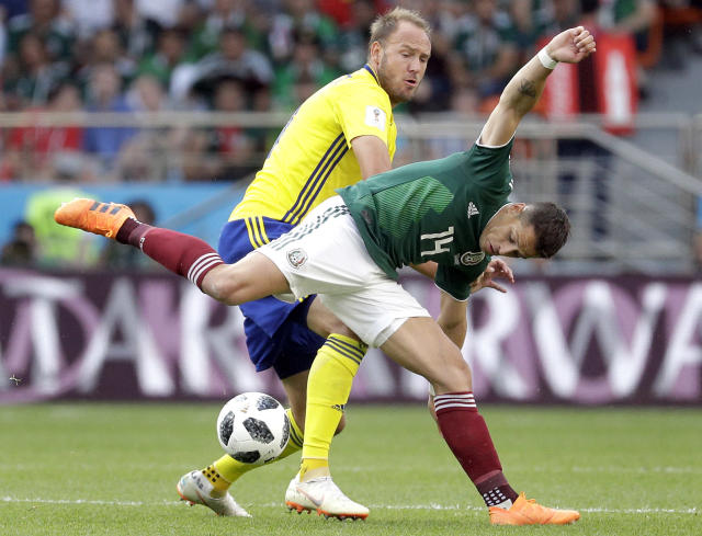 "FILE - In this Wednesday, June 27, 2018 file photo Sweden's Andreas Granqvist, rear, and Mexico's Javier Hernandez, front, challenge for the ball during the group F match between Mexico and Sweden, at the 2018 soccer World Cup in the Yekaterinburg Arena in Yekaterinburg , Russia. FIFA has fined Sweden's soccer federation 70,000 Swiss francs ($70,750) for players wearing unapproved branded clothing. FIFA says the Sweden team defied requests ""to cease the activity that led to the sanction."" (AP Photo/Gregorio Borgia)"
