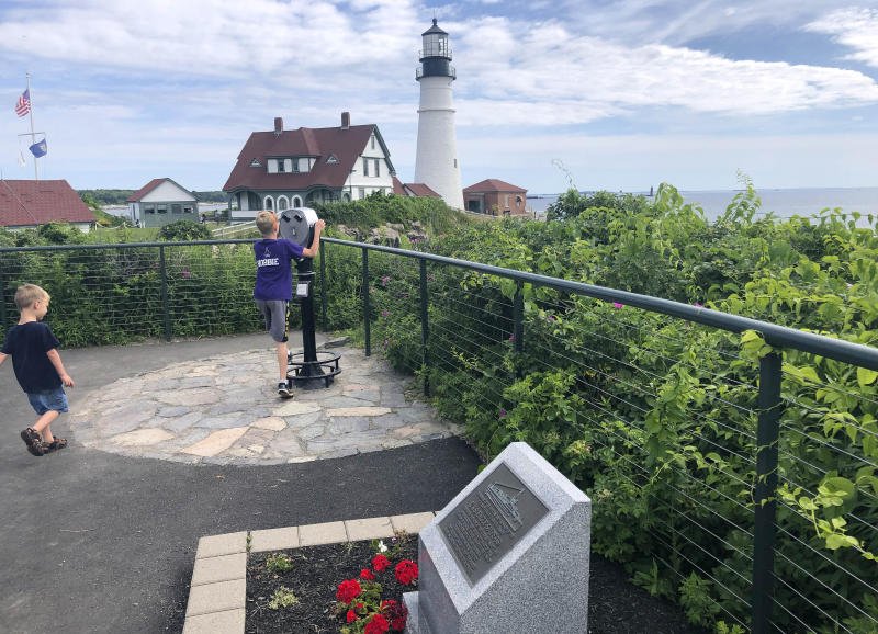 Children take in the view at Fort Williams Park at Cape Elizabeth, Maine, on Thursday, July 18, 2019, where a plaque, foreground, remembers those killed when the USS Eagle PE-56 was sunk During World War II off the Maine coast on April 23, 1945. The Navy determined in 2001 that the patrol boat had been sunk by a German submarine. On Monday, July 15, 2019, Garry Kozak, a specialist in undersea searches, announced that Ryan King, a New Hampshire diver, located the vessel's bow and stern about three miles off Cape Elizabeth in June 2018. (AP Photo/David Sharp)