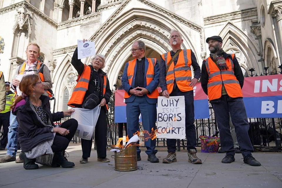 Members of Insulate Britain burnt court orders outside the Royal Courts of Justice (PA) (PA Wire)