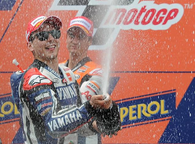 Yamaha Factory Racing's Spanish Jorge Lorenzo (L) and Repsol Honda Team's Spanish Dani Pedrosa (R) celebrate on the podium after the MotoGP race of the Catalunya Moto GP Grand Prix at the Catalunya racetrack in Montmelo, near Barcelona, on June 3, 2012. Yamaha Factory Racing's Spanish Jorge Lorenzo won the race ahead of Repsol Honda Team's Spanish Dani Pedrosa and Monster Yamaha Tech 3 Italian Andrea Dovizioso. AFP PHOTO / LLUIS GENELLUIS GENE/AFP/GettyImages