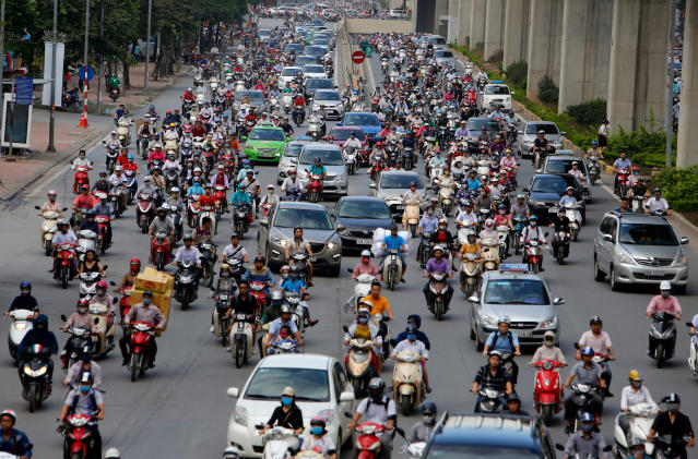 FILE - In this June 21, 2017, file photo, motorbikes and cars fight for space on a street in Hanoi, Vietnam. More Formula One races are coming to Asia, and a street race in the Vietnamese capital Hanoi could be the first addition. Formula One's managing director of commercial operations tells The Associated Press that Hanoi could be added for the 2020 season, though there has been some speculation it could arrive as early as next season. (AP Photo/Tran Van Minh, File)