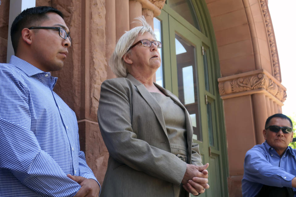 FILE - In this June 28, 2019, file photo, Wendy White, right, speaks at a news conference outside the Coconino County courthouse in Flagstaff, Ariz., as Tremayne Nez, left, looks on. In June 2019, police wrongfully arrested him on suspicion of selling LSD after they mistook Nez, who is Navajo, for the actual suspect, also Native American. After spending more than 30 hours in jail in 2019, he posted bond but his mug shot had already been released, tarnishing his reputation throughout the tribal community. Booking photos taken by police when a person is arrested are often made public, but some experts say releasing someone's mug shot can undermine the presumption of innocence, perpetuate stereotypes and leave a lasting virtual stain.. (AP Photo/Felicia Fonseca, File)