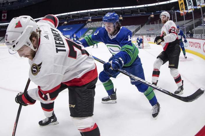 Vancouver Canucks' Quinn Hughes, center, checks Ottawa Senators' Chris Tierney, left, as Senators' Connor Brown watches during the third period of an NHL hockey game Thursday, April 22, 2021, in Vancouver, British Columbia. (Darryl Dyck/The Canadian Press via AP)