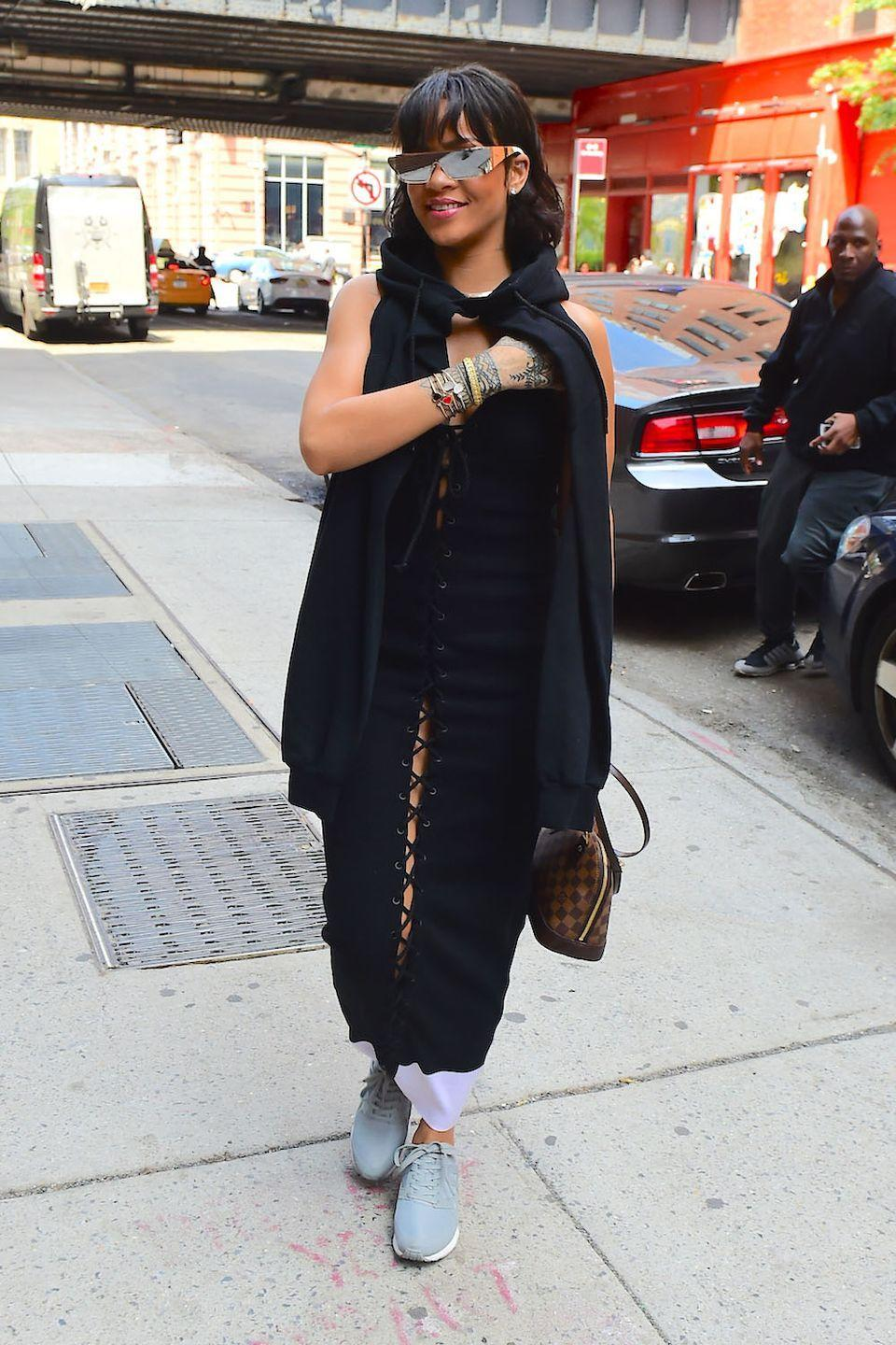 <p>In a black cape and dress with a Louis Vuitton bag, grey sneakers, and her Dior sunglasses collaboration designs </p>