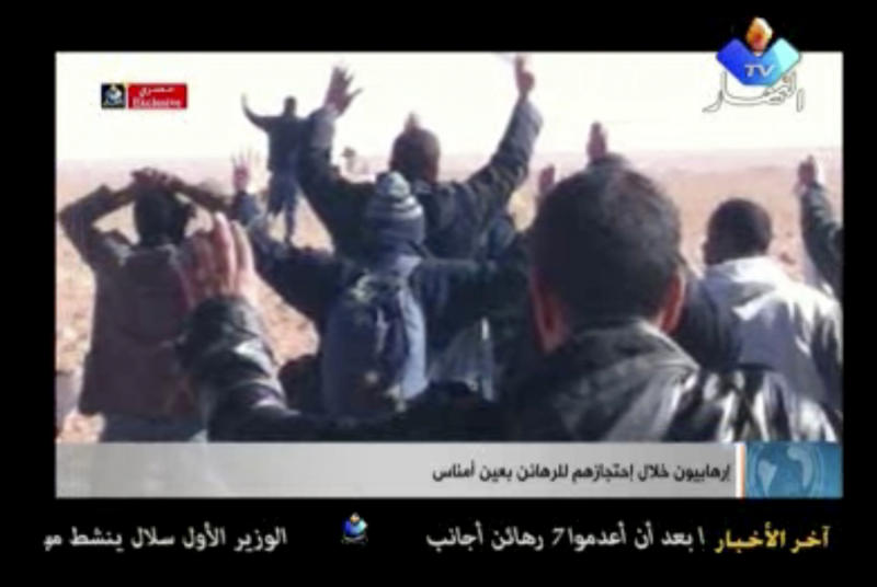 In this image made from video, a group of people believed to be hostages kneel in the sand with their hands in the air at an unknown location in Algeria. Algerian de-mining teams were scouring a gas refinery on Sunday, Jan. 20, 2013 that was the scene of a bloody four-day standoff, searching for explosive traps left by the Islamist militants who took dozens of foreigners hostage. The siege left at least 23 captives dead, and the American government warned that there were credible threats of more kidnapping attempts on Westerners. (AP Photo/Ennahar TV) ALGERIA OUT, TV OUT