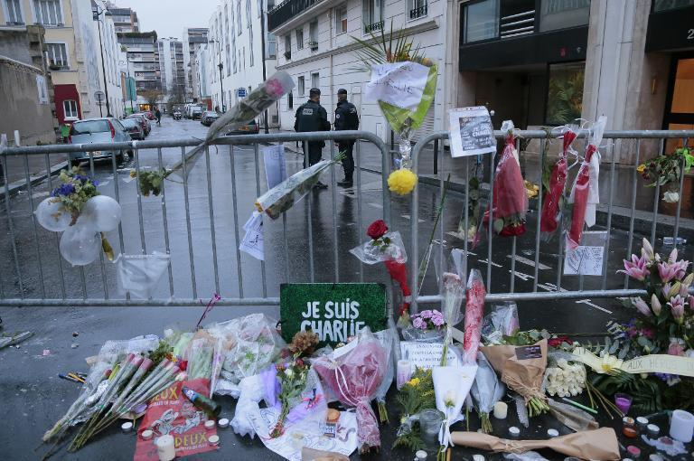 French police stand guard near floral tributes outside the Charlie Hebdo offices in Paris, on January 9, 2015