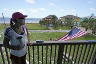 Roberta Holmes, stands on the balcony of her home where she rode out Hurricane Laura, just west of where the eye of the storm made landfall, in Gulf Breeze, La., in the aftermath of the hurricane, Saturday, Aug. 29, 2020. (AP Photo/Gerald Herbert)