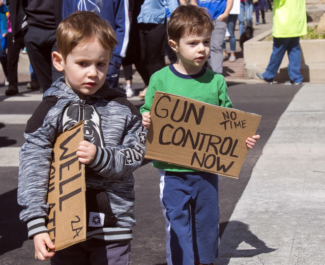 <p>Four-year-old twins Eli, left, and his brother Nathan Hellman hold their signs during the 'March For Our Lives' event in Colorado Springs, Colo. (Dougal Brownlie/The Gazette via AP) </p>
