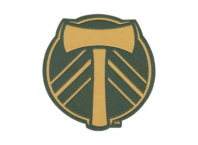 <p>The Timbers have worn an axe (which looks like a 'T') on their jerseys since 1975 and the three chevrons represent more than the evergreen trees of the Pacific Northwest. They stand for the three eras of Portland pro soccer—the NASL days in the 1970s and early '80s, the rebirth and ensuing decade in the second tier and then finally, the 2011 move to MLS. The 2015 champs darkened their green and gold colors ahead of the 2017 season and now sport this crest on their jerseys.</p>