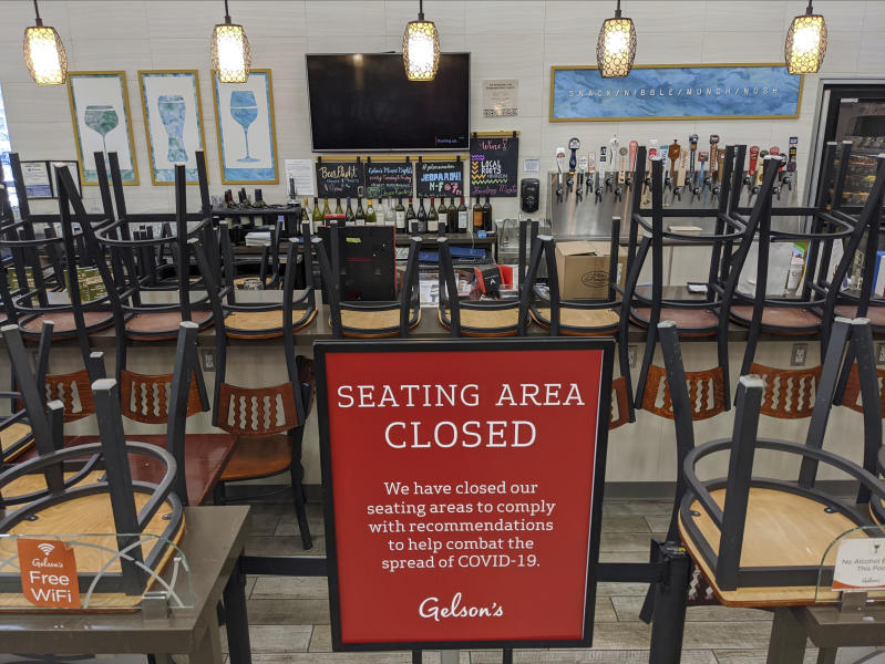 FILE - In this March 26, 2020, file photo, an indoors sitting bar is closed inside the Gelson's Market in Los Feliz neighborhood of Los Angeles. Gov. Gavin Newsom on Sunday, June 28, 2020, ordered bars that have opened in seven California counties to immediately close and urged bars in eight other counties to do the same, saying the coronavirus was rapidly spreading in some parts of the state. The counties under the mandatory bar closure order are: Los Angeles, Fresno, San Joaquin, Kings, Kern, Imperial and Tulare. (AP Photo/Damian Dovarganes, File)
