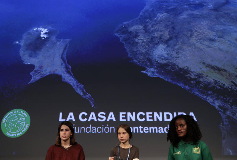 Climate activist Greta Thunberg, centre, attends a press conference in Madrid, Friday Dec. 6, 2019. Thunberg arrived in Madrid Friday to join thousands of other young people in a march to demand world leaders take real action against climate change. (AP Photo/Bernat Armangue)