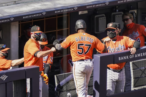 Baltimore Orioles' Hanser Alberto (57) celebrates with staff wearing protective masks after scoring on an RBI single hit by Ryan Mountcastle off New York Yankees starting pitcher Jordan Montgomery in the sixth inning of a baseball game, Saturday, Sept. 12, 2020, in New York. (AP Photo/John Minchillo)