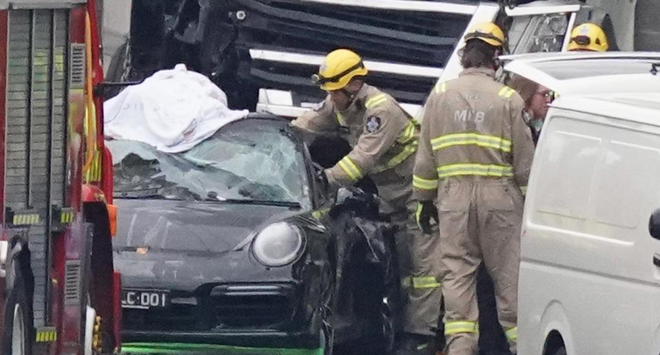 Emergency workers tend to the Porsche following the fatal collision. Source: AAP