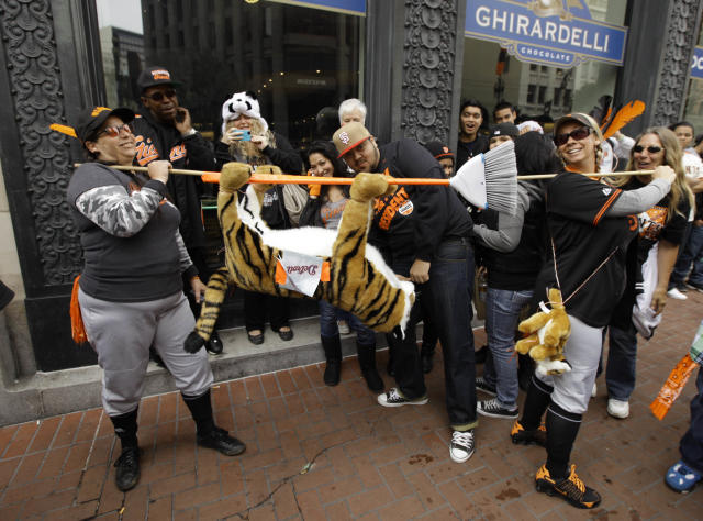DeDe Krake, left, and Stacy Hunt, right, of Auburn, Calif., carry a tiger on a broom while walking along Market Street before the start of the San Francisco Giants World Series victory parade Wednesday, Oct. 31, 2012 in San Francisco. The team's second championship in three years goes along Market Street and ends with a celebration in front of City Hall. (AP Photo/Eric Risberg)