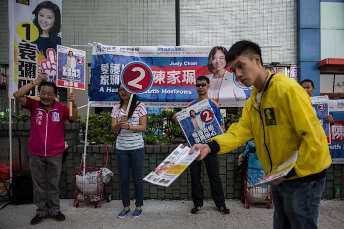 Campaigners (back) for election candidate Judy Chan of the New People's Party hold placards as a campaigner for People Power (from R, in yellow) hands out leaflets near a polling station in the Southern district of Hong Kong on November 22, 2015 (AFP Photo/Anthony Wallace)