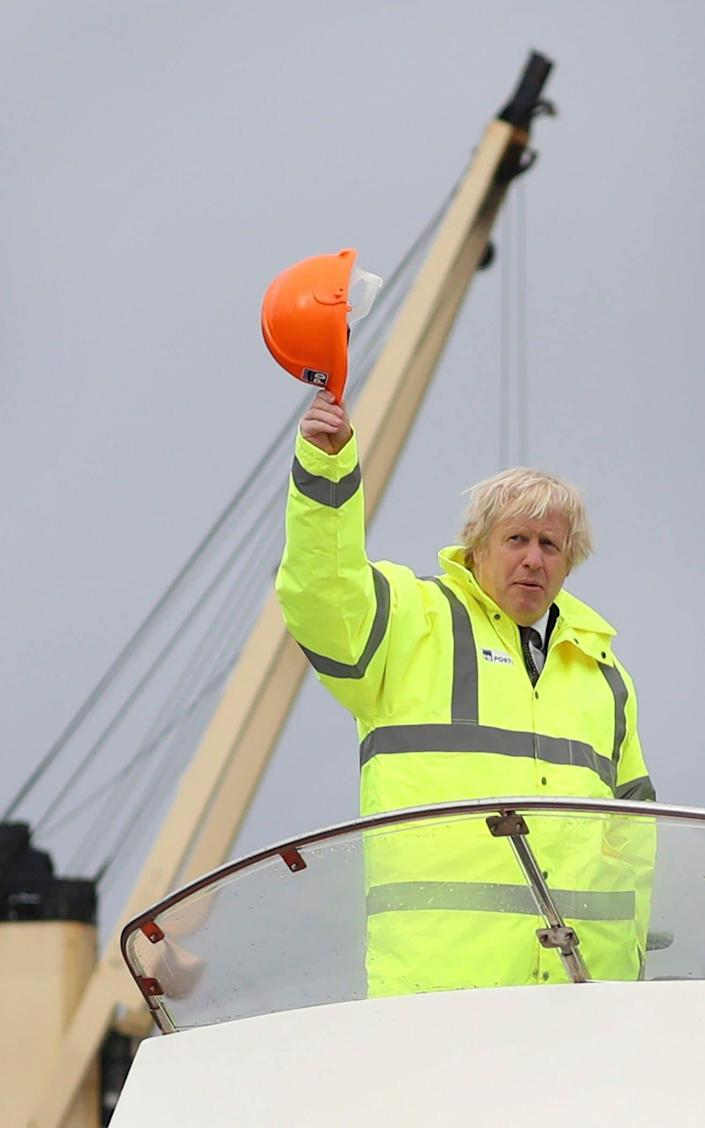 Hard-hat at the ready: Boris Johnson waves from a boat on the River Tees - AP Pool