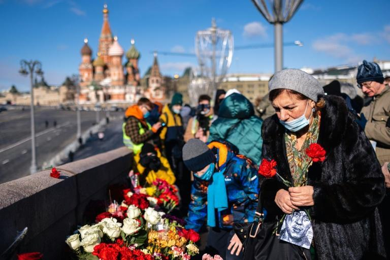 People lay flowers in central Moscow on February 27, 2021 at the site where late opposition leader Boris Nemtsov was fatally shot