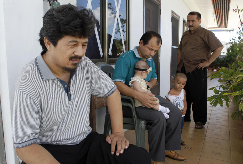 In this photo taken on Feb. 9, 2013, former Guantanamo prisoners, from left, Ahmat Abdulahad, Davut Abdurahim and Abdulghappar Abdulrahman sit outside Abdulrahman's small apartment in Koror, Palau. Released from Guantanamo Bay military prison by the U.S. in 2009, Abdulahad and several other Uighur men have been struggling on the South Pacific island nation of Palau where they have been temporarily resettled. The men and Palau's new president say pressure from China has made it impossible for them to find a permanent home elsewhere. (AP Photo/Eric Talmadge)