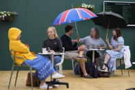 People shelter under umbrellas during a rain delay on day one of the Wimbledon Tennis Championships in London, Monday June 28, 2021. (AP Photo/Kirsty Wigglesworth)