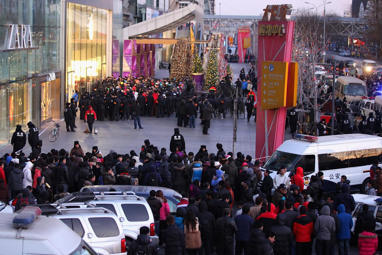 BEIJING, CHINA - JANUARY 13:  Police officers seal off the area near Apple's Beijing flagship store on January 13, 2012 in Beijing, China. Apple with China's leading telecommunications carrier, China Unicom, began to sell Apple's iPhone 4S at the Chinese mainland today.  (Photo by Feng Li/Getty Images)