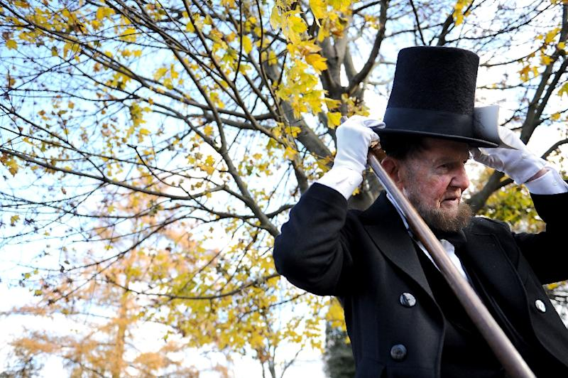 A man portraying US President Abraham Lincoln wears an example of Lincoln's trademark stovepipe hat (AFP Photo/Patrick Smith)