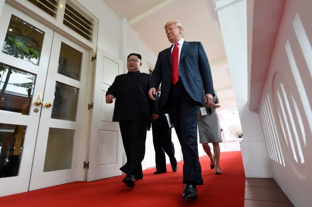 <p>North Korea's leader Kim Jong Un (L) walks with US President Donald Trump (R) at the start of their historic US-North Korea summit, at the Capella Hotel on Sentosa island in Singapore on June 12, 2018. – Donald Trump and Kim Jong Un have become on June 12 the first sitting US and North Korean leaders to meet, shake hands and negotiate to end a decades-old nuclear stand-off. (Photo: Saul Loeb/AFP/Getty Images) </p>