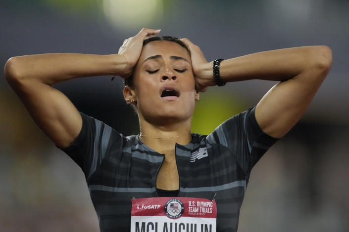 """FILE - In this June 27, 2021, file photo, Sydney McLaughlin reacts after setting a new world record in the finals of the women's 400-meter hurdles at the U.S. Olympic Track and Field Trials in Eugene, Ore. The playbook for athletes provides a guide to a """"safe and successful Games"""" for the Tokyo Olympics. It's filled with """"cannots"""" and """"do nots,"""" meaning a once-in-a-liftetime opportunity will be a whole lot less fun. (AP Photo/Ashley Landis, File)"""