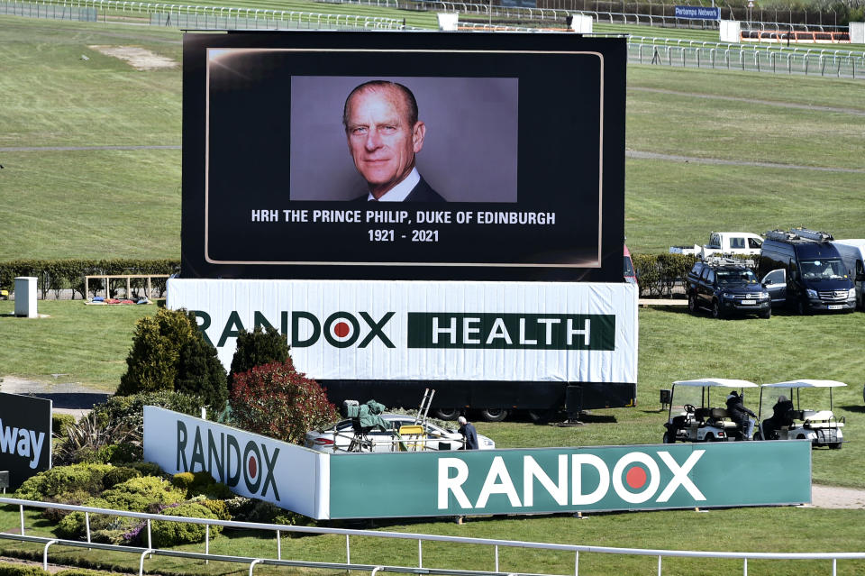 A video screen shows a picture of the late Prince Philip, Duke of Edinburgh, ahead of the races on the second day of the Grand National Horse Racing meeting at Aintree racecourse, near Liverpool, England, Friday April 9, 2021. Buckingham Palace says Prince Philip, the irascible and tough-minded husband of Queen Elizabeth II, has died. He was 99. (Peter Powell/Pool via AP)
