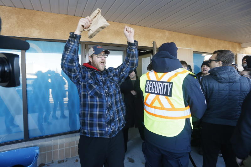 Matthew Dahl celebrates being the first person to buy at a cannabis store in Winnipeg, Manitoba, Wednesday, Oct. 17, 2018. Canada became the largest country with a legal national marijuana marketplace as sales began early Wednesday. (John Woods/The Canadian Press via AP)