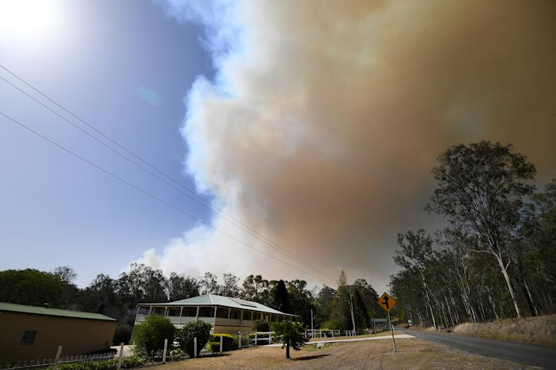 Pictured is smoke from an out-of-control bushfire behind a home near Clumber, Queensland. Source: AAP