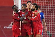 Liverpool midfielder Georginio Wijnaldum (jersey No. 5) is mobbed by teammates after scoring the team's third goal against Chelsea. (PHOTO: Laurence Griffiths/POOL/AFP via Getty Images)