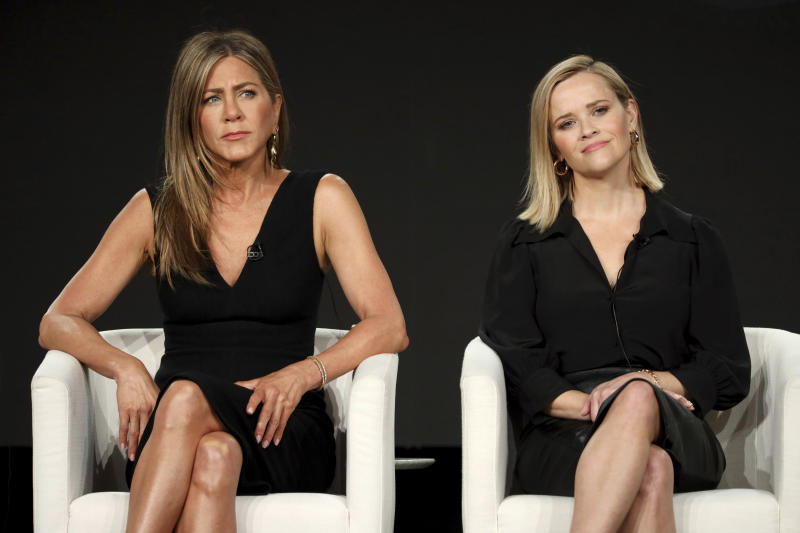"Jennifer Aniston, left, and Reese Witherspoon speak at ""The Morning Show,"" panel during the Apple+ TCA 2020 Winter Press Tour at the Langham Huntington, Sunday, Jan. 19, 2020, in Pasadena, Calif. (Photo by Willy Sanjuan/Invision/AP)"