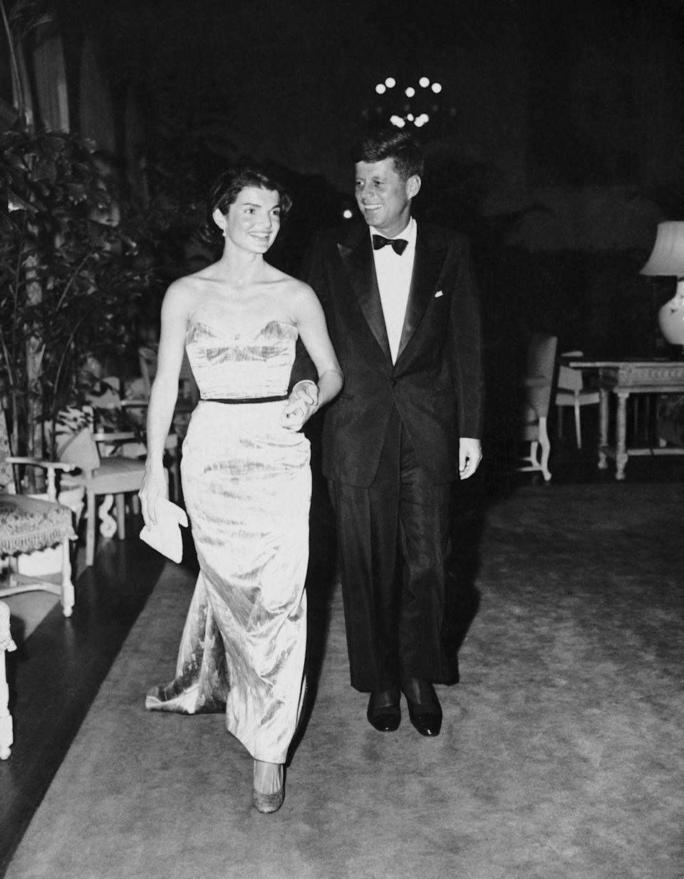 <p>Looking stunning in a metallic strapless and form-fitting gown, Jackie Kennedy walks with her husband, the first Roman Catholic elected as President of the United States. </p>